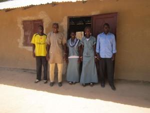 Directeur Mamina (2e van l.) met 2 leerkrachten en 2 leerlingen voor een ingemetselde deur en raam
